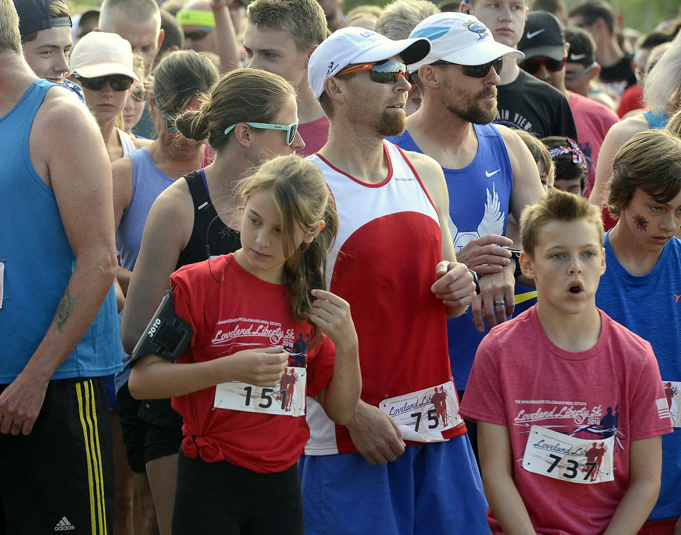 . Hailey Flanigan puts in her headphones as she prepares for the start of Wednesday\'s Liberty 5K at Fairgrounds Park. (Mike Brohard/Loveland Reporter-Herald)