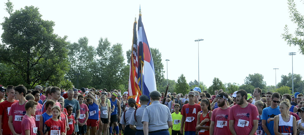 . Liberty 5K runners part as the color guard exits the start area prior to the beginning of Wednesday\'s race at Fairgrounds Park. (Mike Brohard/Loveland Reporter-Herald)