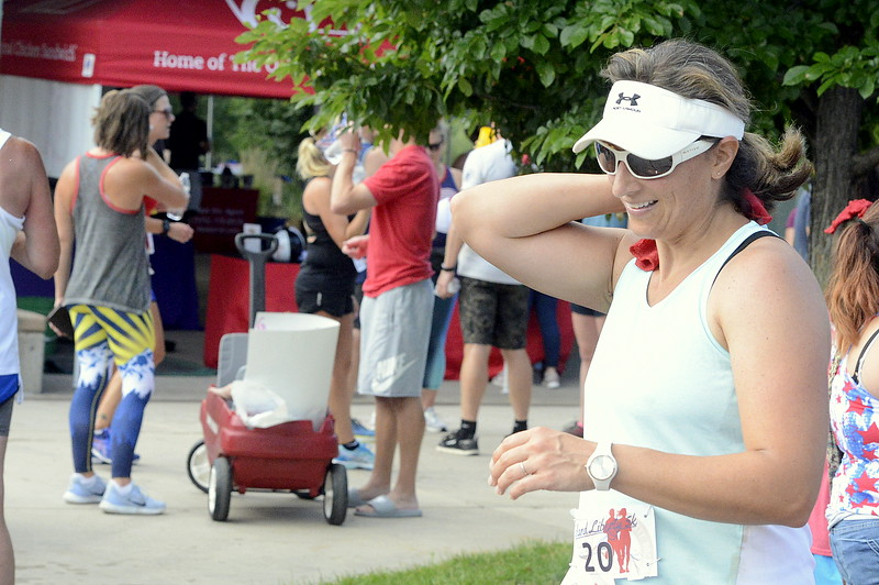 Ann Baker puts a cold towel on her neck after Wednesday's Liberty 5K at Fairgrounds Park. (Mike Brohard/Loveland Reporter-Herald)