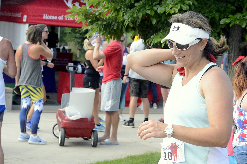 . Ann Baker puts a cold towel on her neck after Wednesday\'s Liberty 5K at Fairgrounds Park. (Mike Brohard/Loveland Reporter-Herald)