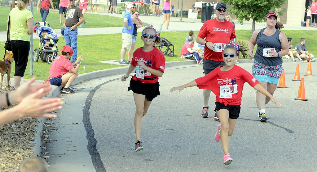 . Eliza and Esther Greenberg are all smiles as the approach the finish of Wednesday\'s Liberty 5K at Fairgrounds Park. (Mike Brohard/Loveland Reporter-Herald)