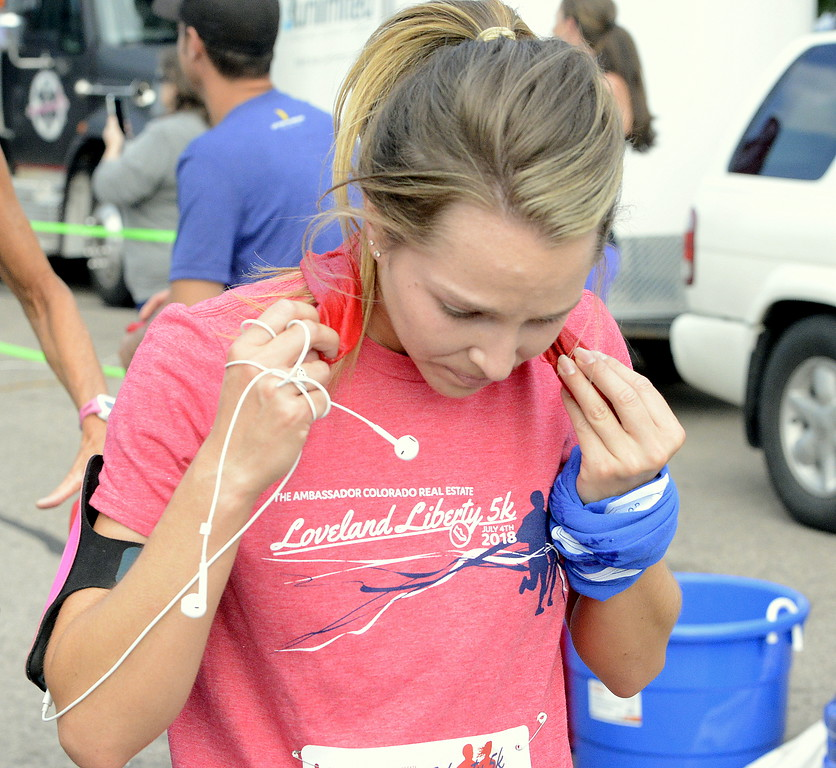 . Madison Ames puts a wet towel on the back of her neck after finishing  Wednesday\'s Liberty 5K at Fairgrounds Park. (Mike Brohard/Loveland Reporter-Herald)
