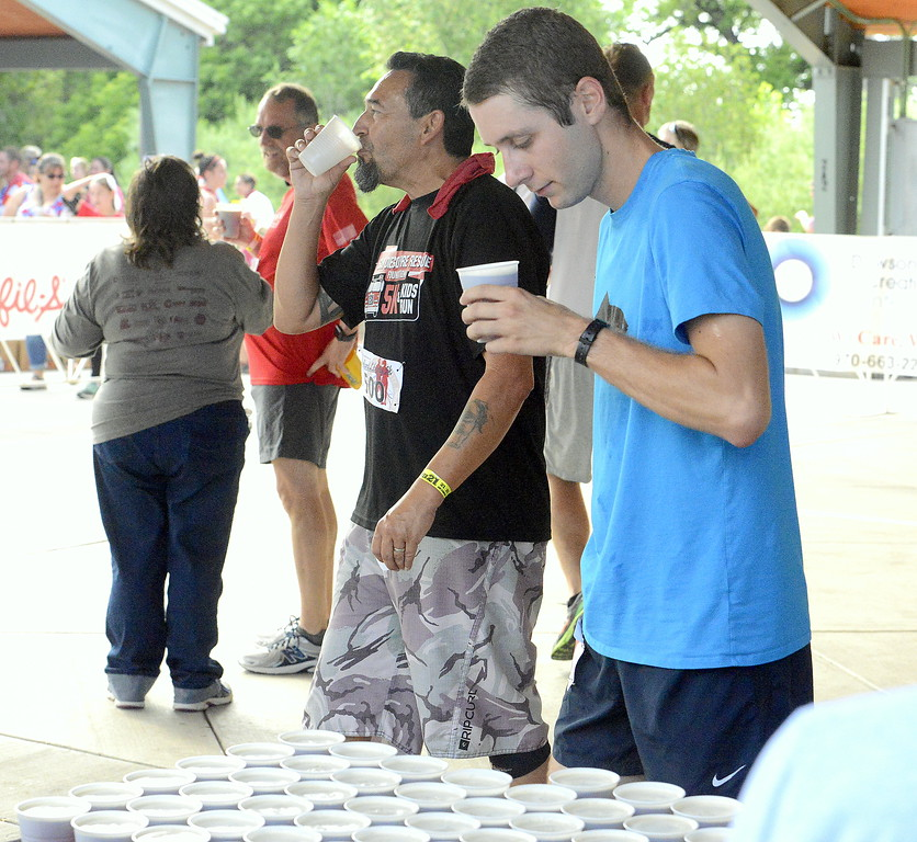 . For the finishers who were old enough, a free, cold beer was welcome at the end of Wednesday\'s Liberty 5K at Fairgrounds Park. (Mike Brohard/Loveland Reporter-Herald)