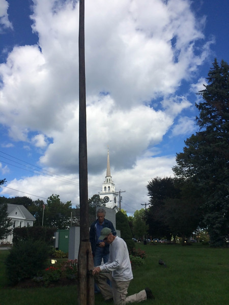 The members of the Billerica Colonial Minute Men dissemble the liberty pole in the Billerica Common to lower it to the ground for maintenance. Photo by Mary Leach