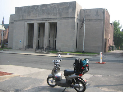 """War Memorial Building, Appleton Street, Holyoke. Home of the Holyoke Council of Aging (among other agencies) and distribution site for the FarmShare program. Electric scooter in foreground loaded with our portable printer, laptop, connecting cables and banner.  The """"roving librarian"""" is ready to roll!"""