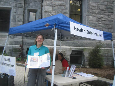 Sandy displays Holyoke Public Library information. Our HCHL booth is promoting information resources for both the National Library of Medicine (MedlinePlus, etc.) and the Holyoke Public Library.