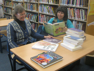 Sandy Ward and Maria Pagan, Library Director,  admire the new books, January 17, 2006.