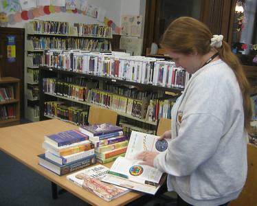 Children's Librarian Carolann MacMaster examines a new book