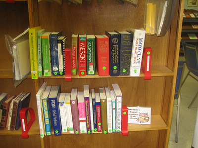 """The Reference shelf as it looked January 20 after Sandy and Doris added some new books and added green """"REF"""" labels."""