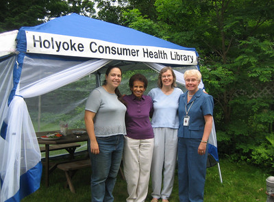 Jennifer Hartley, Doris McKethan, Sandy Ward, and Judy Atkin pose under our new sign and tent.  June 14 celebration at Sandy's home.