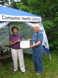 HCHL Treasurers Doris (out-going) and Judy (incoming) pose with the NN/LM check.