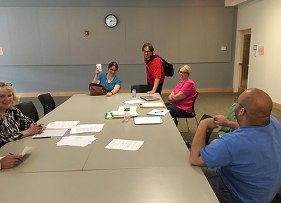 "In June 2017, Sarah Hodge Wetherbe (aka GeekGal) attended a Friends board meeting to speak about Comic-cons, invited by Board member Terrence Smith (in red). Her enthusiasm was contagious.  In August, at Celebrate Holyoke,  we put a sign-up sheet at the Library's table, asking ""Comic-Con? Would you like to help us organize one?"" Ten volunteers signed..."