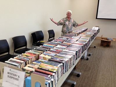 """Helen Wyzga volunteered to help sort and set up for the booksale. We were lucky that the room became available Thursday May 19 (hours earlier than originally planned).   Helen was pleased to have """"finished"""" organizing the Mystery section... (but she didn't know how many more boxes were still stored downstairs)."""