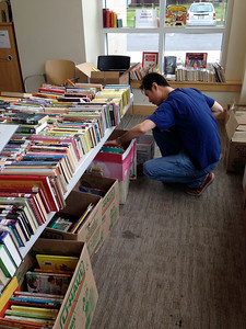 Last minute selections...    This man selected several boxes of children's books to give away during after-school and summer programs at Holyoke Tae Kwon Do.