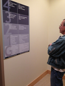 José reads the bilingual directory by the elevator.