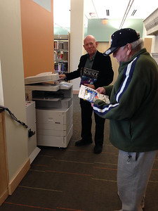Reference librarian Michael Baron helps make a copy for a reader.