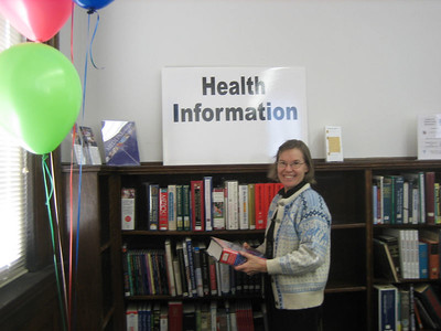 Sandy Ward standing by the health section of the reference collection.  New books have been added, thanks to the HCHL project funded by the National Library of Medicine.