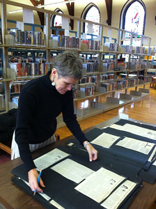 HPL Archivist Eileen Crosby arranging display of materials donated by Barbara C. Bernard. November 2012.
