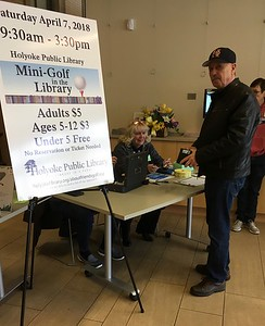 Saturday morning... Min Golf for all ages.  Friends President Karlene Shea at the Ticket Table. Library Board member George Mettey ready to play.