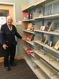 Michael Baron, reference librarian and long-term Friends member, standing by the display in honor of Terry Plum.