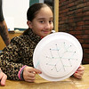 David Rivera watches his daughter Leilaunie Gomez, 9, make a paper plate snow flake with yarn in June Celona's crafts hour at the Fitchburg Public Library on Tuesday February 7, 2017. SENTINEL & ENTERPRISE/JOHN LOVE