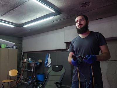 Bitcoin miner Shota Siradze wears anti-static gloves while repairing malfunctioning mining equipment in his office. Tbilisi, Republic of Georgia. Photo: Joe Harrison.