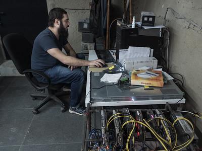 Bitcoin miner Shota Siradze working in his office in the basement of an apartment building. Tbilisi, Republic of Georgia. Photo: Joe Harrison.