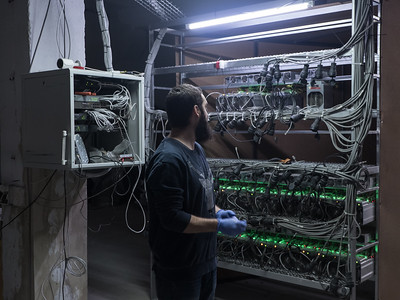 """Bitcoin miner Shota Siradze inspects a rack of bitcoin mining units wearing anti-static gloves. The components, all imported from China, include hashing boards, cooler fans and a power unit. """"[A mining unit] is actually doing the same as a computer does, but it doesn't give you a user interface,"""" says Siradze. """"It does a specific calculation it was given on the day it was built, it can do only that. It finds the block, it finds the transaction and approves that transaction – and that's how we are getting our bitcoins."""" Tbilisi, Republic of Georgia. Photo: Joe Harrison."""