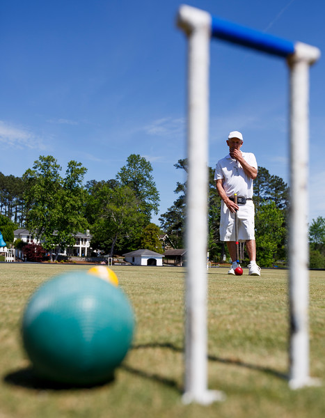 Nadav Soroker/Times-Georgian<br /> <br /> Allen Griffin plans a shot at James Huff's regulation-size croquet field, one of the only in Georgia, in his backyard on Lake Carroll, on Wednesday, April 24, 2019. Huff, a nationally ranked Golf Croquet player, hosts regular games as well as visiting players from around the country and beyond.