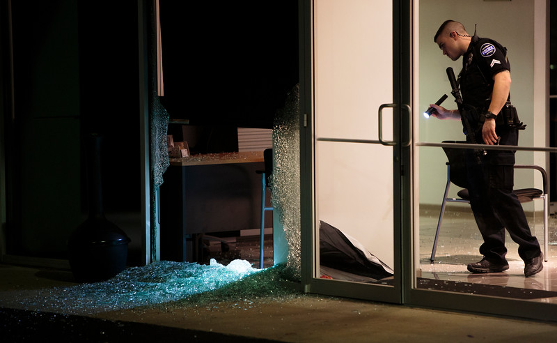Nadav Soroker/Times-Georgian<br /> <br /> Carrollton Police Corporal Josh Perry examines shattered glass at the John Thornton car dealership after a break-in on the night-shift from Friday night to Saturday morning, on Friday, March 22, 2019.