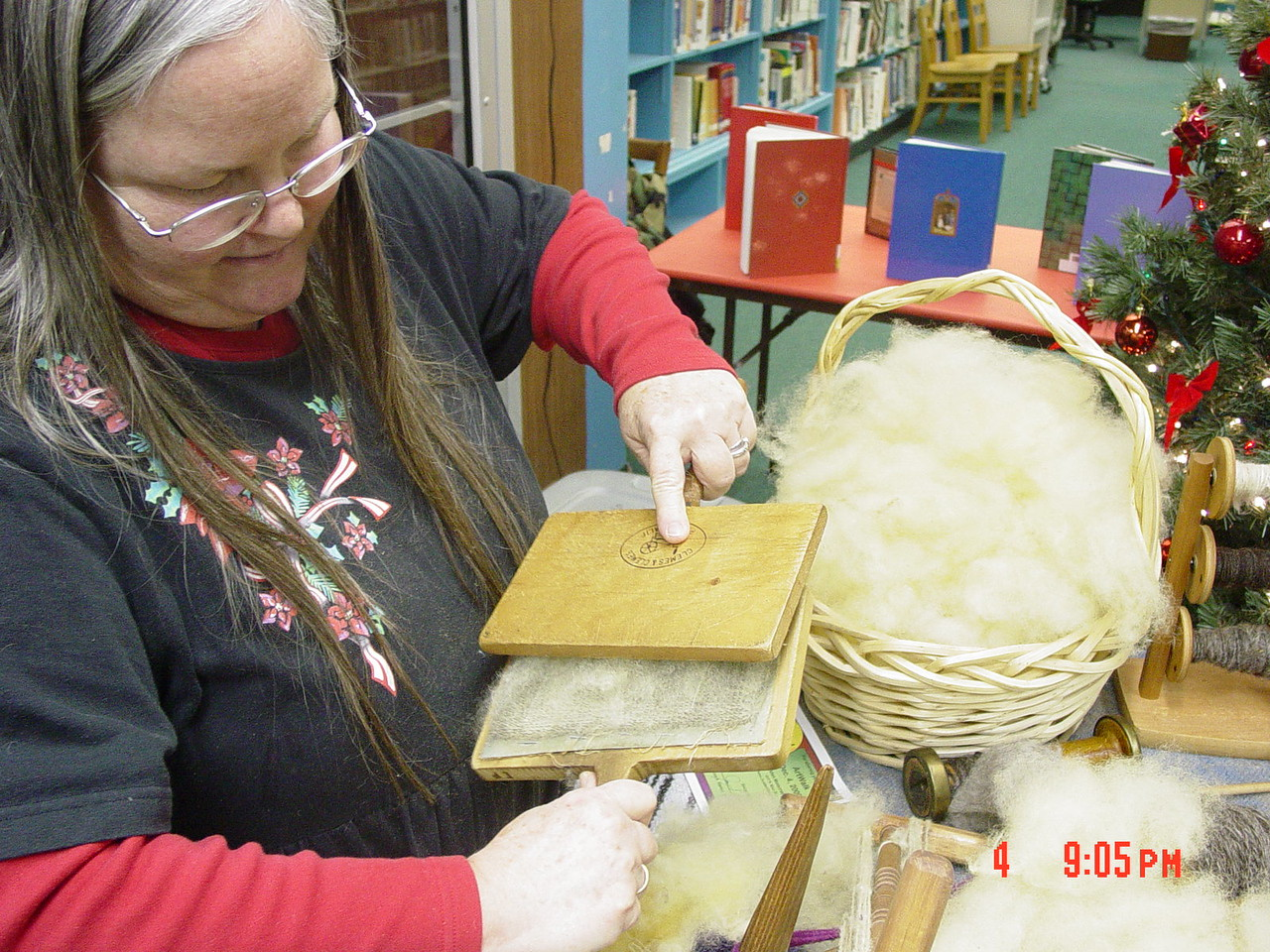 Elizabeth Perdomo demonstrating the process of wool carding.