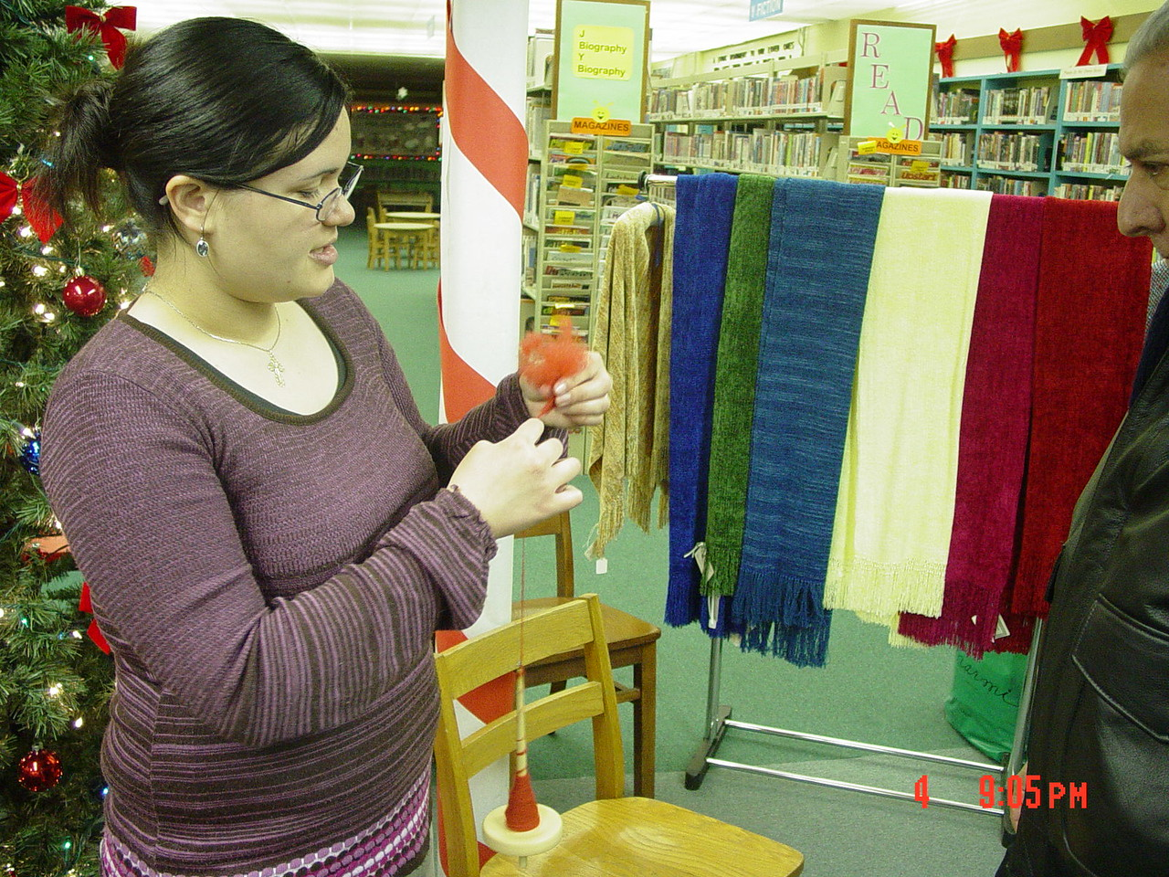 Cristina Perdomo showing an artwalker the next step in processing wool into yarn.