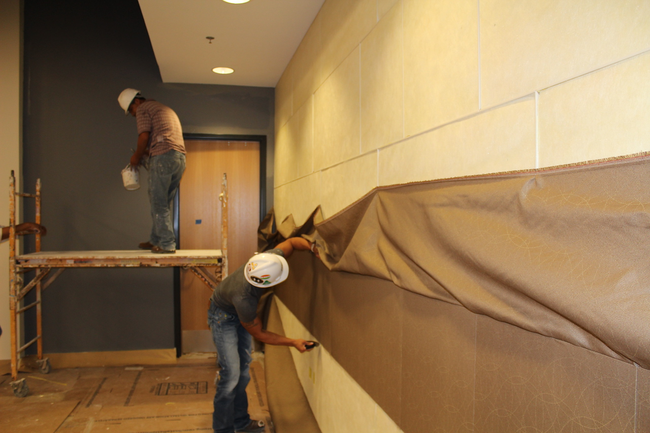 Workers applying custom-made fabric to a wall inside Meeting Rooms A & B.