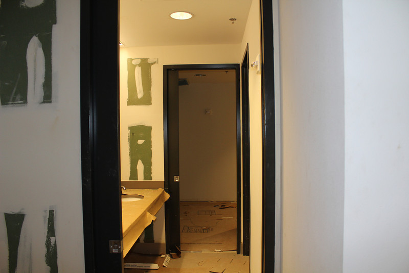 The two green rooms behind the auditorium, featuring a shared sink and a bathroom with shower stall and toilet.