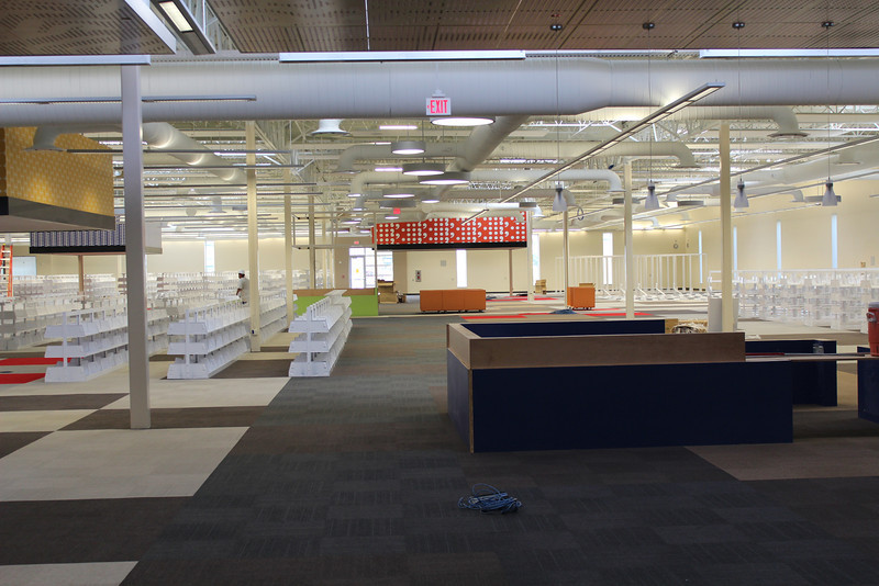 north (blue) info desk in background and south (green) info desk in background under red mega-pendant. white shelves will hold the circulating adult collections (fiction, nonfiction, Spanish, Texas, New Arrivals, and more).