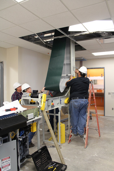 Workers installing the materials handling system located in the circulation department workroom behind the loan desk.