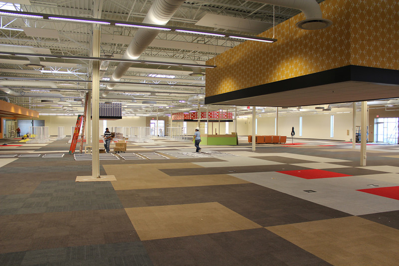 A view of the adult collection area with the mega-pendants in place and the white shelving units being constructed.