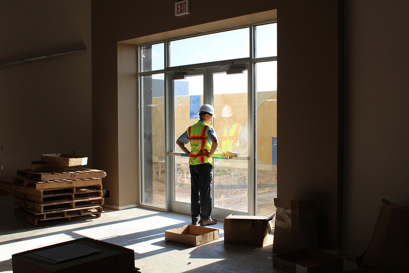 Library Director Jose Gamez inspects the outdoor children's courtyard from inside the children's section.