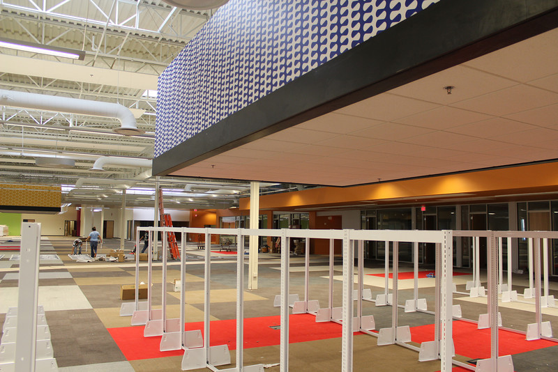 White shelving units being constructed beneath one of the mega-pendants in the adult collection area.
