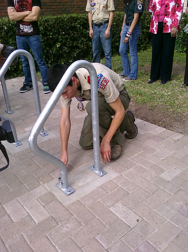 Eagle Scout, Arnold Martinez, securing the bike rack onto the cement.