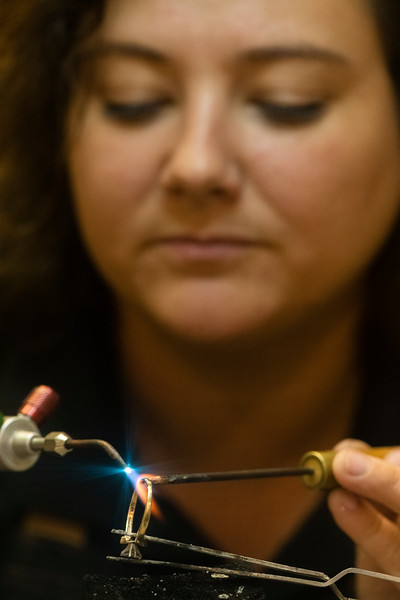 Molly Smith uses her oxy-acetylene torch to solder a gold ring as part of a custom repair order, Thursday morning, Sept. 26, 2019.