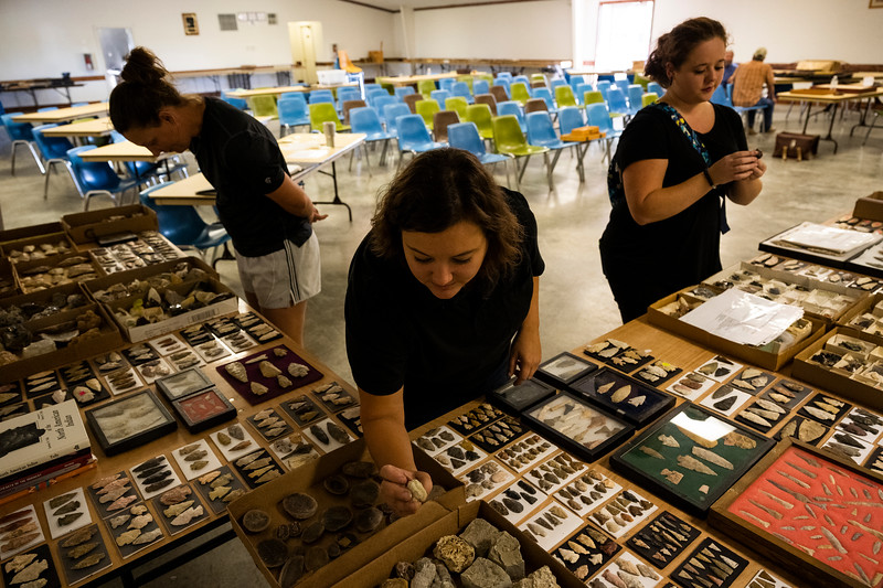 Molly Smith, center, and Sarah Darnell preview an auction to see if there are any pieces that Smith might want for her store at the Cooper County Fairgrounds on Thursday afternoon, Sept. 26, 2019. Smith found several pieces, including some large mineral pieces to decorate her display cabinets.