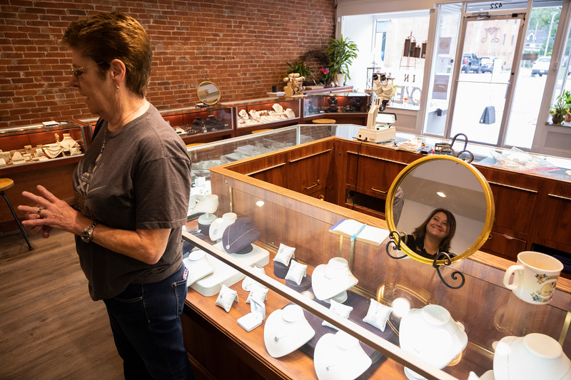 Molly Smith, reflected in a mirror on the right, helps a customer in the showroom of her store, Wednesday, Sept. 25, 2019.