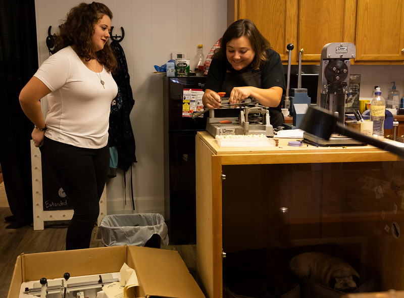 Molly Smith, right, helps her hew assistant Sarah Darnell set up the engraver so she can practice in the jewelry store's workroom, Wednesday, Sept. 25, 2019. Smith is training Darnell so she can do the easier tasks like cleaning and engraving jewelry, leaving Smith to focus on her more complicated custom orders.