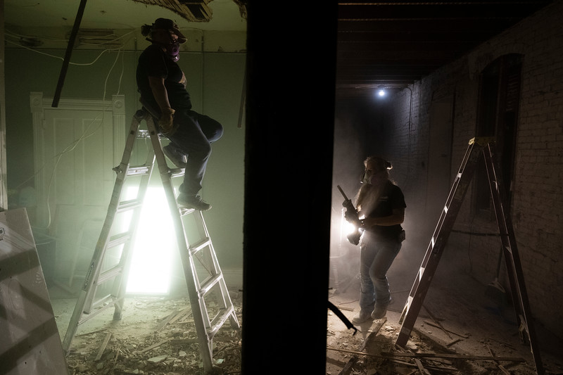 Molly Smith, left, works with Erica Counts to knock down an interior wall of the kitchen in the apartment above her store, Thursday night, Sept. 26, 2019. Smith and Counts are renovating the space for future use.