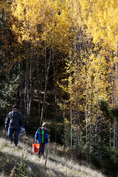 David Falasca and his son Nihar, 8, carry trash out of a stand of aspens on Sunday, Oct. 1, 2017. 50 volunteers showed up for the Creek Week cleanup, up from 36 the previous year.<br /> <br /> (The Gazette, Nadav Soroker)