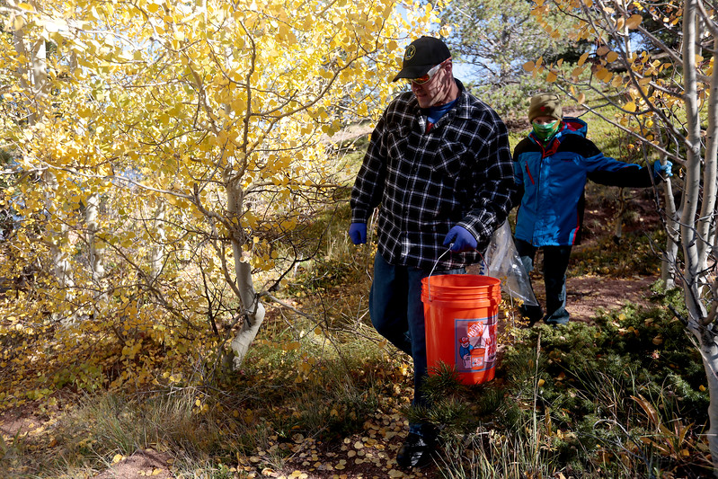 David Falasca and his son Nihar, 8, navigate a rough path along the south shore of Crystal Creek Reservoir on Sunday, Oct. 1, 2017. Volunteers walked the shores and paths around the reservoirs filling backs and buckets with trash.<br /> <br /> (The Gazette, Nadav Soroker)