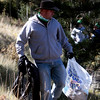 Eric Blohm carries a bag of trash and a torn up tire back towards the parking lot at Crystal Creek Reservoir on Sunday. Volunteers collected more than 12 bags of trash from Crystal Creek, North Catamount and South Catamount reservoirs.<br /> <br /> (The Gazette, Nadav Soroker)