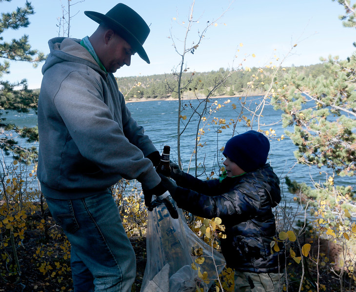Kenny Blohm, 5, throws two beer bottles into the trash bag his father, Eric, holds open on the south shore of Crystal Creek Reservoir on Sunday. The cleanup at the reservoirs was part of a week-long event taking place throughout the Fountain Creek Watershed.<br /> <br /> (The Gazette, Nadav Soroker)