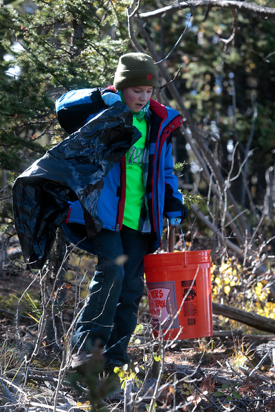 Nihar Falasca, 8, pulls a trash bag from a pine tree south of Crystal Creek Reservoir on Sunday, Oct. 1, 2017. Nihar is a bear scout with Troop 73 in Colorado Springs.<br /> <br /> (The Gazette, Nadav Soroker)